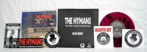 "The Hymans - Rocker (7"" vinyl, booze002, leather bag edition: transparent purple vinyl with black splatter, 20 copies. + The Hymans sticker, The Hymans iron-on sticker, The Hymans 1"" pin, Bootleg Booze Records sticker, Bootleg Booze Records iron-on sticker, Bootleg Booze Records 1"" pin, Flyer signed by The Hymans)"